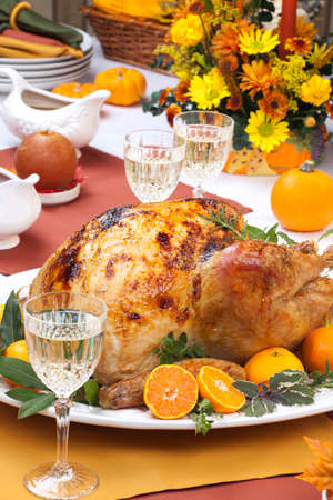 thanksgiving dinner: Garnished citrus glazed roasted turkey on holiday table, pumpkins, flowers, and white wine