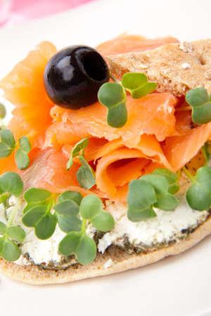 queso de cabra: Detalle de delicioso bocadillo de cara abierta con salmón ahumado, queso de cabra y daikon coles. Foto de archivo