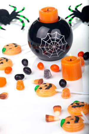 Halloween candy scattered around, candles, and spiders. photo