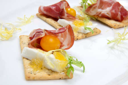 canapes: Crackers with goat cheese, apricot spread, and yellow pear tomatoes wrapped to prosciutto