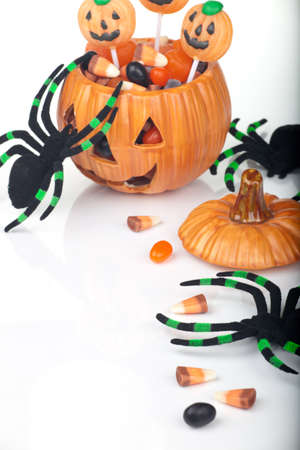 Halloween candy scattered around, fall beries, leaves and spiders. photo