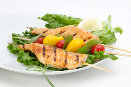 Closeup of grilled salmon on bamboo sticks and vegetable skewers with fresh tarragon and green salad