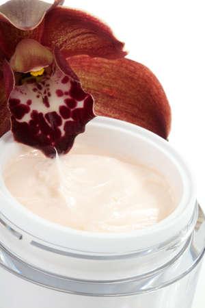 cremas faciales: Detalle de tarro de crema facial y flor de orquídea Cymbidium color chocolate blooming Foto de archivo