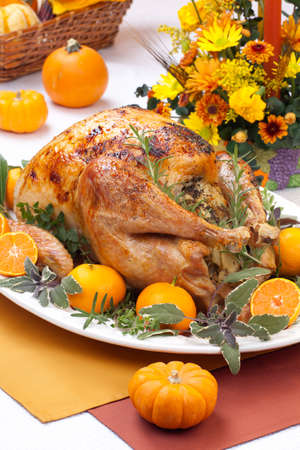 stuffing: Garnished citrus glazed roasted turkey on holiday table, pumpkins, flowers, and white wine