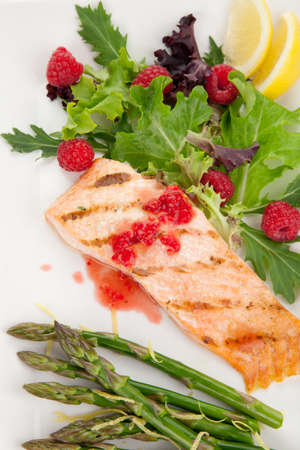 Grilled salmon with raspberry dressing served with asparagus and green salad, healthy meal. photo