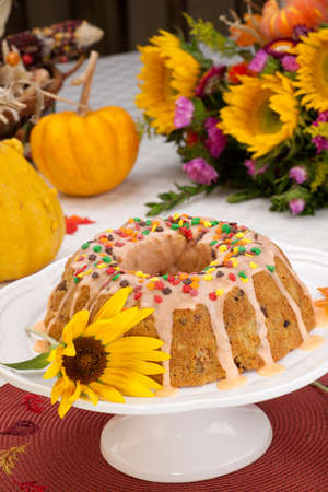 Fall cake with autumn leaves sprinkles over citrus icing, decorated with pumpkins and Indian corn Stock Photo