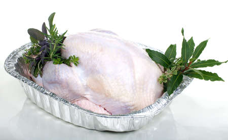 Closeup of raw uncooked turkey in roasting dish garnished with lemons, and aromatic herbs. photo