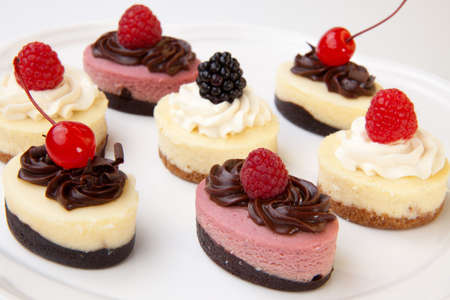 Full tray of delicious fresh cheesecakes garnished with frosting and berries.