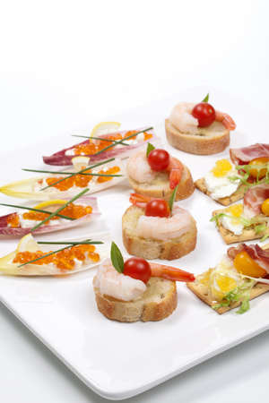 Assorted fresh canapes on tray ready for holiday table over white background photo