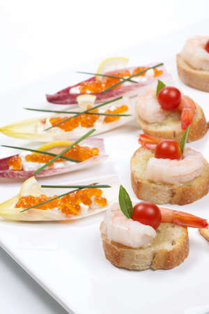 canapes: Assorted fresh canapes on tray ready for holiday table over white background