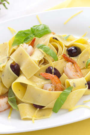 Shrimp lemon pepper Pappardelle pasta with fresh basil, and black olives. photo