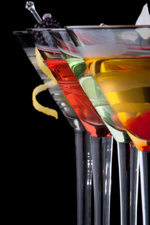 Classical martini in chilled glass over black background on reflection surface, garnished with freah blackberry, maraschino cherry, marinated pearl onoions, olive and lemon twist. Most popular cocktails series. Stock Photo - 10627271