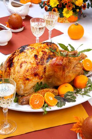 Garnished citrus glazed roasted turkey on holiday table, pumpkins, flowers, and white wine