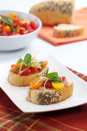 yelllow: Closeup of two delicious yelllow, red, and orange tomato Bruschetta garnished with Parmesan cheese and fresh basil leaves.