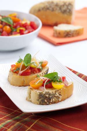 Gros plan de deux d�licieux yelllow, rouge, orange et la tomate Bruschetta garni de fromage parmesan et de feuilles de basilic frais. Banque d'images - 10693188