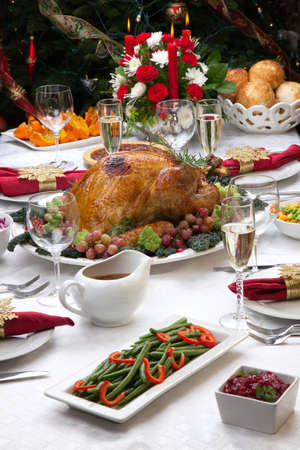 feast: Holiday-decorated table, Christmas tree, champagne, and roasted trurkey.