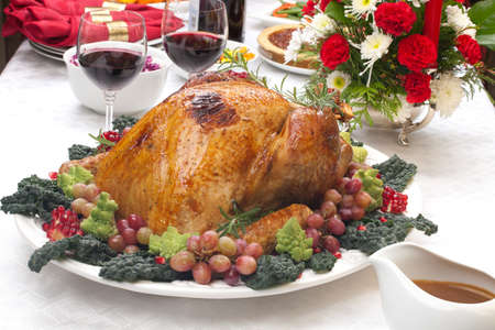 Holiday-decorated table, Christmas tree, champagne, and roasted trurkey. photo