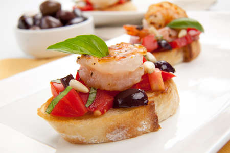 Closeup of delicious Olive - Tomato Bruschetta with garlic shrimp and pine nuts. Stock Photo