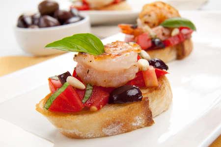 pignons de pin: Gros plan de d�licieuses olives - Tomate Bruschetta aux crevettes � l'ail et les pignons.
