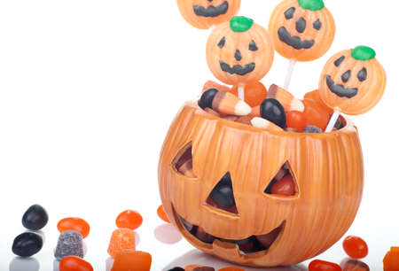 Halloween candy scattered around and in a pumpkin shaped bowl photo