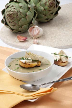 mascarpone: Bowl of artichoke soup garnished with Mascarpone and marinated artichoke crostini.
