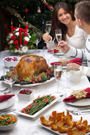 feast: Young couple celebrates Christmas turkey dinner by the Christmas tree.