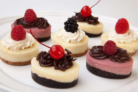 maraschino: Full tray of delicious fresh cheesecakes garnished with frosting and berries.