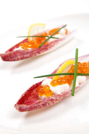 endivia: Primer plano de caviar rojo en Creme Fraiche en el interior de color rojo escarola de hoja canapé en blanco. Foto de archivo