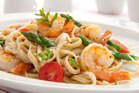 seafood dinner: Healthy whole grain linguine with shrimps, asparagus, cherry tomatoes, fresh Parmesan cheese, and  oregano.