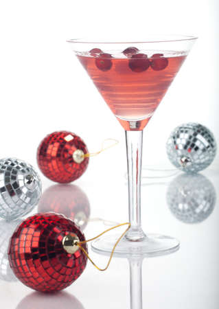 Close up of glass of Limomcello Cosmo Cocktail over white, arranged Christmas ornament. Most popular cocktails series. photo