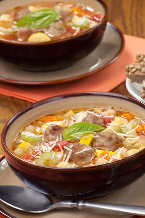 Two bowls of hot fresh  Italian Meatball Soup and wholegrain bread photo