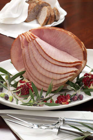 Dinning table set with glazed whole baked sliced ham, garnished with pomegranate, olives, and red pears. Imagens