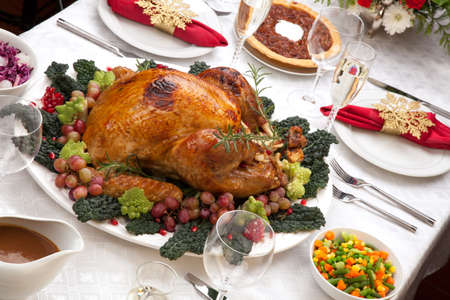 christmas turkey: Holiday-decorated table, Christmas tree, champagne, and roasted turkey. Stock Photo