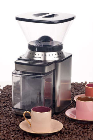 Closeup of modern coffee grinder with coffee beans around over white