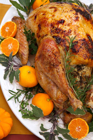 thanksgiving dinner: Garnished citrus glazed roasted turkey on holiday table, pumpkins, flowers, and white wine  Stock Photo