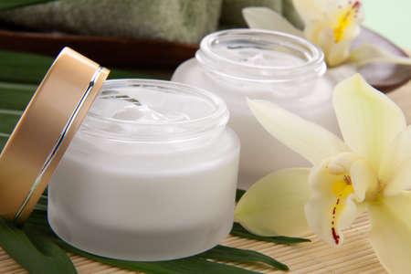 cremas faciales: Blanca flor de la orquídea Cymbidium y tarro de crema hidratante facial para tratamiento de spa.