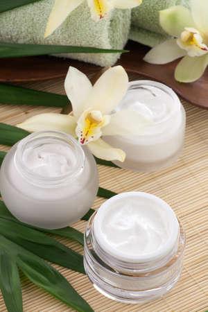 White Cymbidium orchid flower and jar of moisturizing face cream for spa treatment.