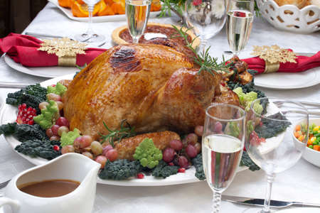 feasts: Holiday-decorated table, Christmas tree, champagne, and roasted turkey. Stock Photo