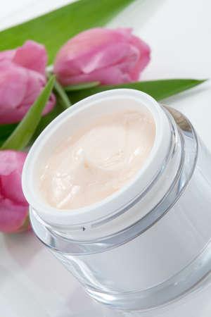 cremas faciales: Primer plano de tarro de crema hidratante cara rodeada de flores de tulipán rosa