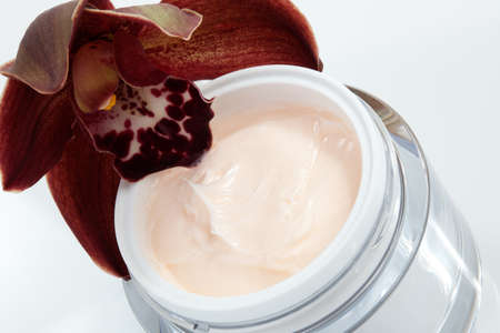 Closeup of jar of face cream and blooming chocolate colored Cymbidium orchid flower