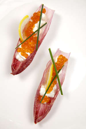 endive: Closeup of red caviar on Creme Fraiche inside red endive leaf canape on white.