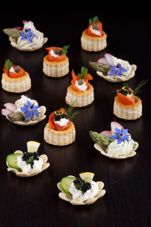 Assorted mini canapes of black caviar on Creme Fraiche, smoked salmon, and  cheese and fresh garden vegetables over black background. Stock Photo - 11769706