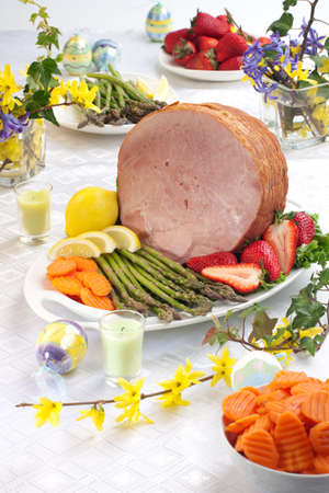 Festive glazed ham for Easter celebration dinner garnished with asparagus, carrots, strawberry, and lemon wedges. photo
