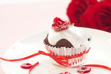 Chocolate muffin garnished with sugar frosted rose and vanilla icing. Valentine photo