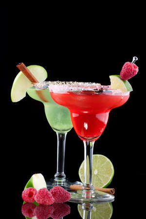 shaken: Apple and Raspberry margaritas in chilled glass over black background on reflection surface, garnished slice of green apple, fresh raspberries, slice of lime and cinnamon stick. Most popular cocktails series.