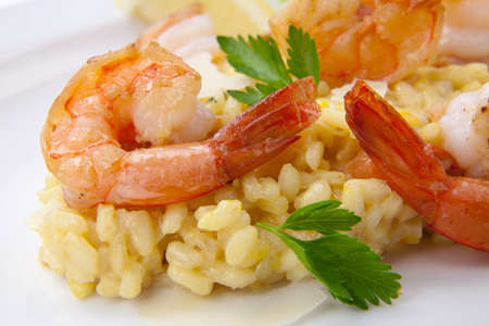 Plate of Shrimps Risotto garnished with fresh parsley and Parmesan cheese. photo