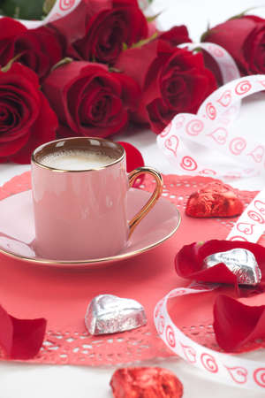 Closeup of cup of fresh coffee with red roses on Valentines day.