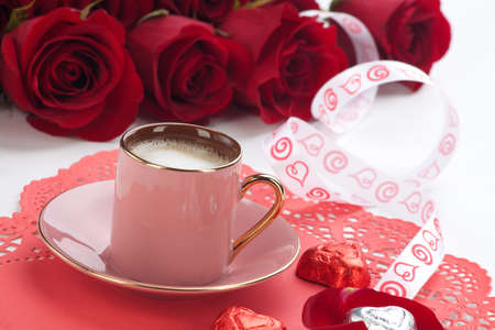 Closeup of cup of fresh coffee with red roses on Valentines day. photo