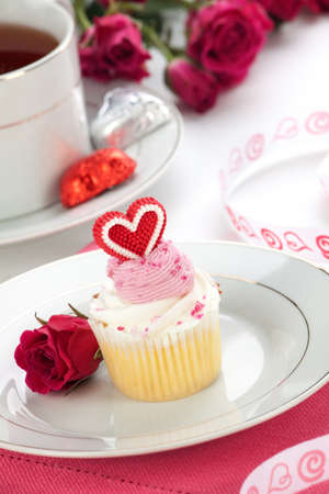 Closeup of cream cupcake on Valentine day with heart shaped decoration. Tea and pink spray roses. photo