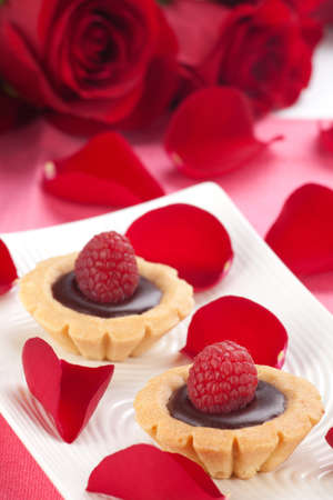 chocolate cakes: Closeup of delicious fresh raspberry chocolate petite cakes on Valentine day. Red roses and petals around.